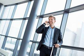 businessman_speaking_phone_airport_cg1p04634731c_th